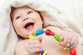 picture of baby toddler  - Small smiling baby with a toy - JPG
