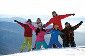 Happy snowboarding team in winter mountains