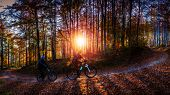 Cycling woman and men riding on bikes at sunset autumn mountains forest landscape. Couple cycling MT poster