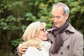 old couple wearing warm clothes in the forest and expressing tenderness