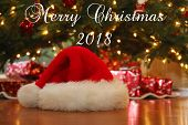 Christmas Image. Santa Claus hat lays on a wooden floor with reflections of a Christmas tree in the  poster
