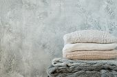 Pile Of Knitted Throw Blankets And Plaids On Shabby Gray Background. Warm Cosy Home Decor poster