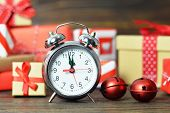 New Year Countdown. Midnight Clock And Gift Boxes On Wooden Background poster