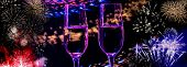 Two Glasses Of Wine Sizzling Champagne With Bubbles Close-up On The Background Of Colorful Fireworks poster