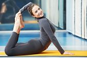 Happy smiling woman at gymnastic physical training fitness exercise in gym