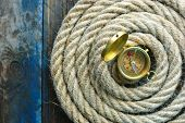Nautical Navi Background. Rope With A Compass On A Weathered Wooden Desk. poster