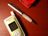Pen And Cellular Phone On Desk