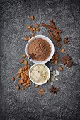 Top View Of Cocoa Powder And Almond Slices In White Bowls With Spices poster
