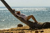 Beautiful Woman Relaxing On Palm Tree On The Beach. Healthy People Lifestyle. Woman Relaxing On The  poster