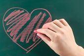 Drawing heart on the chalkboard.