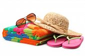 Beach items with straw hat,towel,flip flops and sunglasses.Isolated on white background.