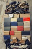 A Stack Of Folded Cardboard Boxes And A Lot Of Variety Of Shoes On The Background Of The Shabby Wall poster