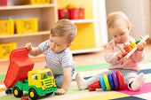 Kids Playing With Educational Toys. Children Sit On A Rug In A Play Room At Home Or Kindergarten. To poster