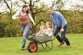 Eltern geben Kindern zu Reiten, In Schubkarre