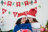 Asian Lover Girl Friend Give Christmas Gift At Xmas Party,asia Girl Friends Wear Santa Hat Exchange  poster