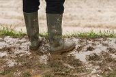 A Person In Rubber Boots Standing In The Mud. poster