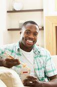Jovem homem relaxante sentado no sofá a comer a refeição chinesa em casa