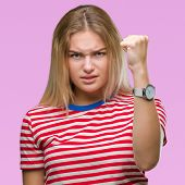 Young caucasian woman over isolated background angry and mad raising fist frustrated and furious whi poster