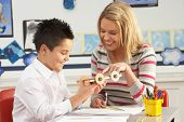 stock photo of student teacher  - Male Primary School Pupil And Teacher Working At Desk In Classroom - JPG