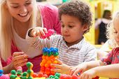 stock photo of daycare  - Young woman playing with boy - JPG