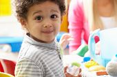 image of daycare  - Boy playing with toys in nursery - JPG