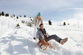 foto of toboggan  - Young Couple Sledding - JPG