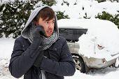 junger Mann im Schnee mit aufgeschlüsselt Auto