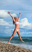 Cute Young Woman Jumping With Her Arms In The Air While At The Beach