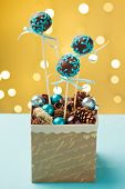 picture of cake pop  - Chocolate cake pops garnished with turquoise icing sticking in nice Christmas gift box. Very shallow depth of field with Christmas lights in the background