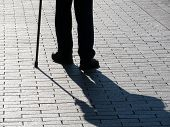 Silhouette Of Limping Man Walking With A Cane, Long Shadow On Pavement. Concept For Disability, Old  poster