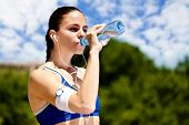 thirsty sporty woman drinking water after training
