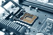 stock photo of cpu  - Empty cpu processor socket on a computer motherboard with pins visible - JPG