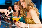 stock photo of bartender  - Young people in club or bar drinking cocktails and having fun - JPG