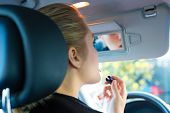 Young woman with lipstick in car looks into review mirror