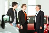 Mature single man with autos in light car dealership with a young couple, he obviously is buying a car or is a car dealer