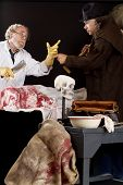 stock photo of jekyll  - Evil doctor interacts with grave robber over bloody corpse - JPG