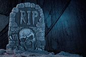 stock photo of tombstone  - Tombstone with skull on dark background halloween party decoration - JPG