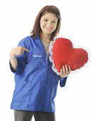 Voluntário adolescente feliz, segurando um travesseiro em forma de coração, ao apontar para a palavra