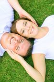 stock photo of soulmate  - two caucasian couple lay down on grass looking up - JPG
