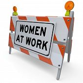 The words Women at Work on a road construction sign symbolizing a woman's equal rights in the workforce and the female gender working together toward a common goal of progress