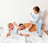 a young family lying in bed in the bedroom