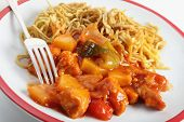 Chicken sweet and sour on a plate with chinese noodles and a fork