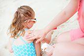 Mother applying sunblock cream on her daughter shoulder