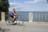 Woman Cyclist Passing A Lake View