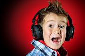 Expressive little boy in headphones is singing a song.