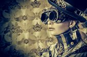 stock photo of cyborg  - Portrait of a beautiful steampunk woman over vintage background - JPG