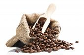 pic of coffee crop  - coffee beans on brown bag with wooden spoon isolated on white background - JPG