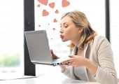stock photo of kiss  - picture of woman with laptop computer sending kisses and hearts - JPG