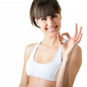 sport young woman with perfect body show ok gesture, fitness girl studio shot over white background