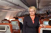 blonde businesswoman in black suit staying in airplane